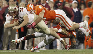 Photo - Florida State tight end Nick O'Leary (35) runs the ball against Clemson linebacker Spencer Shuey, top, and safety Travis Blanks, bottom, during the second half of an NCAA college football game, Saturday, Oct. 19, 2013, in Clemson, S.C. (AP Photo/Mike Stewart)
