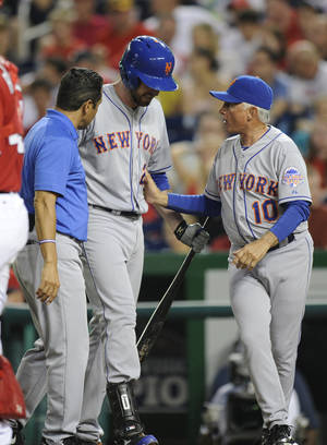 Photo - New York Mets' Ike Davis, center, is tended to by a trainer and manager Terry Collins (10) as he leaves the game after being injured batting during the third inning of a baseball game against the Washington Nationals, Saturday, Aug. 31, 2013, in Washington. (AP Photo/Nick Wass)