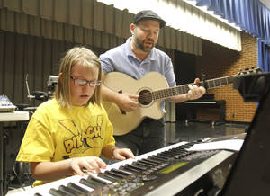 photo - Danielle Mader, 10, plays piano as the Rev. Mark Tullis looks on during a music lesson at Mark Twain Elementary School. Photo by Jim Beckel, The Oklahoman