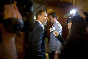 Photo - Australian Prime Minister Tony Abbott, center, is questioned by a Chinese TV reporter about the missing Malaysian Airlines Flight 370 after a press conference at a hotel in Beijing, China Saturday, April 12, 2014. With no new underwater signals detected, the search for the missing Malaysian passenger jet resumed Saturday in a race against time to find its dying black boxes five weeks after families first learned their loved ones never arrived at their destination. (AP Photo/Andy Wong)