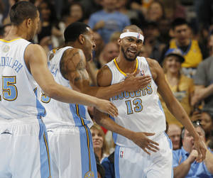 photo - From left, Denver Nuggets forward Anthony Randolph joins guard Andre Iguodala in congratulating forward Corey Brewer after he made a basket and drew a shooting foul against the Los Angeles Lakers in the first quarter of an NBA basketball game in Denver on Monday, Feb. 25, 2013. (AP Photo/David Zalubowski)
