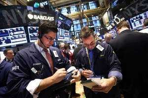 Photo - Traders Thomas Donato, left, and Ronald Madarasz work on the floor of the New York Stock Exchange Friday, Jan. 24, 2014.  (AP Photo/Jason DeCrow)