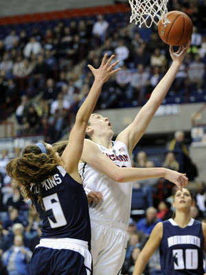 Photo - Connecticut's Breanna Stewart (30) drives past Monmouth's Mia Hopkins during the first half of an NCAA college basketball game, in Storrs, Conn., on Saturday, Nov. 23, 2013. (AP Photo/Fred Beckham)