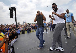 Photo - FANS / NBA BASKETBALL: James Harden, front right, laughs as Derek Fisher, left, speaks during a welcome home rally for the Oklahoma City Thunder in a field at Will Rogers World Airport after the team's loss to the Miami Heat in the NBA Finals, Friday, June 22, 2012. At right in the background is Serge Ibaka. Photo by Nate Billings, The Oklahoman