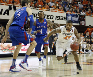 Photo - Oklahoma State 's Marcus Smart (33) drives past Kansas' Jeff Withey (5) and Naadir Tharpe (1) during the college basketball game between the Oklahoma State University Cowboys (OSU) and the University of Kansas Jayhawks (KU) at Gallagher-Iba Arena on Wednesday, Feb. 20, 2013, in Stillwater, Okla. Photo by Chris Landsberger, The Oklahoman