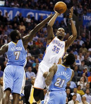 Photo - Oklahoma City's Kevin Durant shoots against Denver's J.J. Hickson and Wilson Chandler during Monday night's game at Chesapeake Energy Arena. Photo by Nate Billings,  The Oklahoman