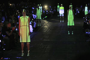 photo -   Models, illuminated by black light, pose in the finale of the Alexander Wang Spring 2013 collection, during Fashion Week in New York, Saturday, Sept. 8, 2012. (AP Photo/Richard Drew)