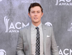 Photo - FILE - This April 6, 2014 file photo shows singer Scotty McCreery at the 49th annual Academy of Country Music Awards in Las Vegas. Police say McCreery was the victim of an early morning home invasion near the campus of North Carolina State University, where he is a student. Raleigh Police spokesman Jim Sughrue says officers were called shortly before 2 a.m. Monday, May 5, to an apartment about a mile from campus. Three suspects armed with guns are reported to have taken wallets, cash and electronic items. (Photo by Al Powers/Powers Imagery/Invision/AP, File)