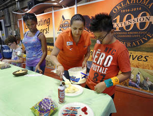 Photo -  Diana Romano delivers scoops of ice cream to contestants in the ice cream sundae contest. At right is Mucio Davila, 10, of Oklahoma City. His decoration was awarded second place in his age division. The fair featured competitions in many categories including photography, woodworking, horticulture, knitting, flower arranging and quilting. Photo by Jim Beckel, The Oklahoman  <strong>Jim Beckel -   </strong>