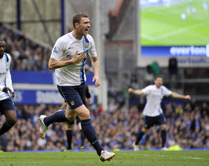 Photo - Manchester City's Edin Dzeko celebrates after he scored the second goal of the game for his side during their English Premier League soccer match against Everton at Goodison Park in Liverpool, England, Saturday May 3, 2014. (AP Photo/Clint Hughes)