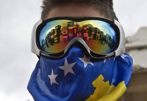 "photo - A Kosovo Albanian youth wearing ski goggles and a Kosovo flag stands near the ""NEWBORN"" monument painted with flags of the countries that have recognized Kosovo's independence marking the 5th anniversary since Kosovo seceded from Serbia in capital Pristina on Sunday, Feb. 17, 2013. Serbia rejects Kosovo independence. (AP Photo/Visar Kryeziu)"