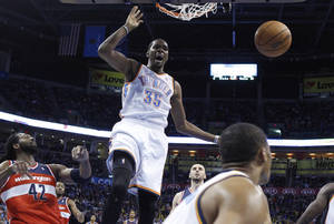 Photo - Oklahoma City Thunder forward Kevin Durant (35) reacts after dunking between Washington Wizards forward Nene (42) and center Marcin Gortat, right, in the first quarter of an NBA basketball game in Oklahoma City, Sunday, Nov. 10, 2013. (AP Photo/Sue Ogrocki)
