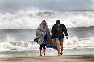 Photo -   McKayla Walker and her mother, Holly, fight the wind and enjoy their first time to see hurricane waves on the Atlantic Ocean, Saturday, Oct. 27, 2012 in Atlantic Beach, N.C. (AP Photo/The Jacksonville Daily News, Chuck Beckley)