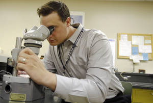 Photo - Waite Colbaugh, a public health specialist of the Consumer Protection Division, studies mosquitos through a microscope on Monday, June 24, 2013. Photo by Aliki Dyer, The Oklahoman