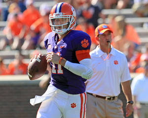 Photo - Clemson quarterback Chad Kelly, left, runs a play in front of head coach Dabo Swinney, right, during an NCAA college football spring game at Memorial Stadium in Clemson, S.C., Saturday, April 12, 2014. (AP Photo/Anderson Independent-Mail, Mark Crammer) GREENVILLE NEWS OUT; SENECA NEWS OUT