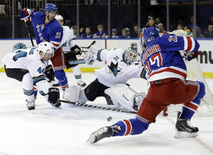Photo - San Jose Sharks goalie Antti Niemi (31), of Finland, and Marc-Edouard Vlasic (44) stop a shot on goal by New York Rangers' Ryan McDonagh (27) during the second period of an NHL hockey game on Sunday, March 16, 2014, in New York. (AP Photo/Frank Franklin II)