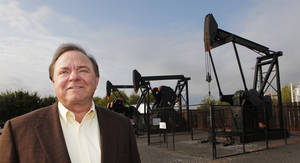 photo - Harold Hamm, CEO of Continental Resources, stands near some of the company's pump jacks. Photo by David McDaniel, The Oklahoman
