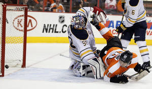 Photo - Philadelphia Flyers' Brayden Schenn, right, looks back to see his shot go in the net past Buffalo Sabres goalie Nathan Lieuwen, left, during the second period of an NHL hockey game, Sunday, April 6, 2014, in Philadelphia. (AP Photo/Tom Mihalek)
