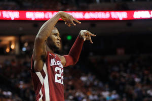 "Photo - Oklahoma's Amath M'Baye signals ""horns down"" to the Texas crowd after a dunk in the second half of an NCAA basketball game in Austin, Texas on Feb. 27, 2013.  (AP Photo/The Daily Texan, Lawrence Peart) ORG XMIT: TXADT101"