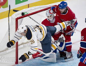 Photo - Buffalo Sabres' Zemgus Girgensons (28) collides with Montreal Canadiens' goaltender Peter Budaj, center, as Canadiens' Matt Lashoff defends during the second period of an NHL pre-season hockey game, Sunday, Sept. 15, 2013 in Montreal. (AP Photo/The Canadian Press, Graham Hughes)