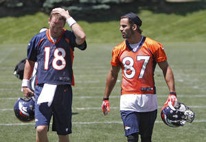 Photo -   Denver Broncos quarterback Peyton Manning (18) and wide receiver Eric Decker (87) talks as they walk off of the field after NFL football practice at the team's training facility in Englewood, Colo., on Wednesday, May 30, 2012. (AP Photo/Ed Andrieski)