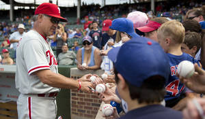 Photo - Philadelphia Phillies interim manager Ryne Sandberg, left,  signs autographs for fans before a baseball game against the Chicago Cubs on Saturday, Aug. 31, 2013, in Chicago. (AP Photo/Andrew A. Nelles)