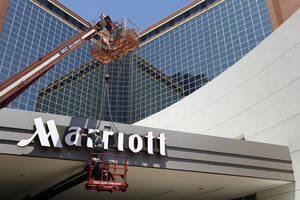Photo - FILE - In this , Tuesday, April 30, 2013, file photo, a man works on a new Marriott sign in front of the former Peabody Hotel in Little Rock, Ark. Marriott reports quarterly earnings on Wednesday, Oct. 30, 2013. (AP Photo/Danny Johnston, File)