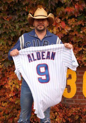 Photo -   Country singer Jason Aldean poses with a Chicago Cubs baseball shirt during a news conference at Wrigley Field to announce his 2013 Night Train Tour on Thursday, Oct. 18, 2012, in Chicago. (Photo by Barry Brecheisen/Invision/AP)