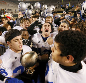 Photo - The Guthrie Bluejays celebrate with the gold ball trophy after winning the 5A state high school football championship game against the McAlester Buffaloes at Boone Pickens Stadium in Stillwater, Okla., Saturday, Dec. 14, 2013. Guthrie won, 51-21. Photo by Nate Billings, The Oklahoman