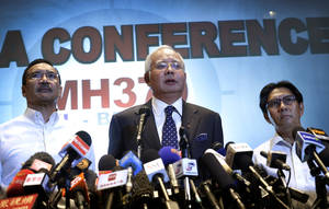 Photo - Malaysian Prime Minister Najib Razak, center, Malaysia's Minister for Transport Hishamuddin Hussein, left, and director general of the Malaysian Department of Civil Aviation, Azharuddin Abdul Rahman, delivers a statement to the media regarding the missing Malaysia Airlines jetliner MH370, Saturday, March 15, 2014 in Sepang, Malaysia. Najib said Saturday that investigators believe the missing Malaysian airliner's communications were deliberately disabled, that it turned back from its flight to Beijing and flew for more than seven hours. (AP Photo/Wong Maye-E)