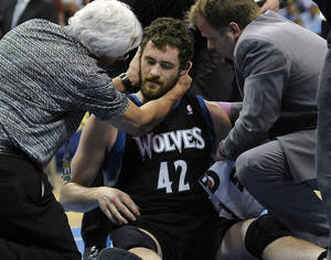 Photo - Minnesota Timberwolves forward Kevin Love was examined by a doctor after he took a shot to the head during the first half of an NBA basketball game against the Denver Nuggets in Denver on Wednesday, April 11, 2012. (AP Photo/The Denver Post, Karl Gehring) MAGS OUT  TV OUT ORG XMIT: CODEN301