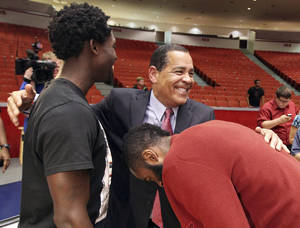 Photo - New Houston NCAA college basketball coach Kelvin Sampson, center, is congratulated by Houston Rockets Patrick Beverley, left, and James Harden during a news conference Thursday April 3, 2014, in Houston, Texas. Houston introduced the former assistant Rockets coach confident that he can bring the once-proud program back to prominence and undeterred by his past improprieties with the NCAA. (AP Photo/Houston Chronicle, Billy Smith II)