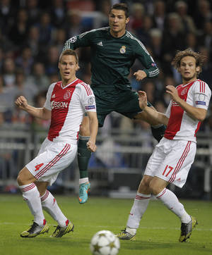 Photo -   Real Madrid player Cristiano Ronaldo, center, and Ajax players Niklas Moisander, left, and Daley Blind, right, vie for the ball during the Champions League Group D soccer match at ArenA stadium in Amsterdam, Netherlands, Wednesday Oct. 3, 2012. (AP Photo/Peter Dejong)