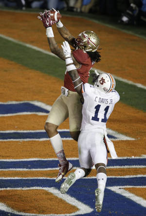 Photo - Florida State's Kelvin Benjamin catches a touchdown pass in front of Auburn's Chris Davis during the second half of the NCAA BCS National Championship college football game Monday, Jan. 6, 2014, in Pasadena, Calif. (AP Photo/Gregory Bull)