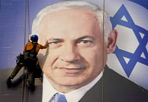 Photo - FILE - In this Thursday, Jan. 17, 2013 file photograph, a worker hangs a huge poster with an image of Israel's Prime Minister Benjamin Netanyahu overlooking the Ayalon freeway in Tel Aviv, Israel. After a lackluster three-month campaign, there seems to be little doubt that Prime Minister Benjamin Netanyahu is on his way to re-election. But the makeup of Netanyahu's next government remains a matter of great uncertainty. (AP Photo/Ariel Schalit, File)
