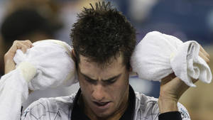 Photo -   John Isner wraps his head with ice wrapped in a towel during his match with Philipp Kohlschreiber, of Germany, in the third round of play at the 2012 US Open tennis tournament, early Monday, Sept. 3, 2012 in New York. The match began on Sunday evening. (AP Photo/Charles Krupa)