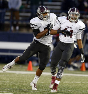 Photo - Edmond Memorial's Chase Kemp, left, and Kourtney Williams celebrate a sack during the high school game between Edmond North and Edmond Memorial at Wantland Stadium in Edmond, Okla., Friday, Sept. 12, 2014. Photo by Sarah Phipps, The Oklahoman