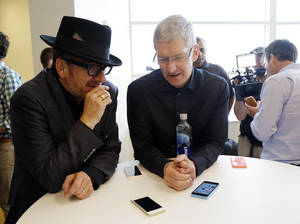 "Photo - Apple CEO Tim Cook, right, speaks with entertainer Elvis Costello after a new product announcement at Apple headquarters on Tuesday, Sept. 10, 2013, in Cupertino, Calif. Apple's latest iPhones will come in a bevy of colors and two distinct designs, one made of plastic and the other that aims to be ""the gold standard of smartphones"" and reads your fingerprint. (AP Photo/Marcio Jose Sanchez) ORG XMIT: FX151"
