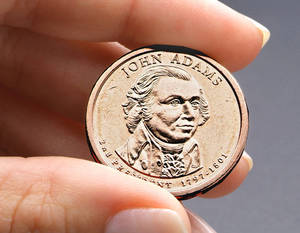 Photo - FILE - This undated file photo provided by the U.S. Mint shows the President John Adams presidential $1 coin. Congressional auditors say doing away with dollar bills entirely and replacing them with dollar coins could save taxpayers some $4.4 billion over the next 30 years. (AP Photo/US Mint, File)