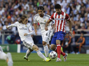 Photo - Real's Luka Modric,left and Real's Sami Khedira, centre, fight for the ball with Atletico's Diego Costa, during the Champions League final soccer match between Atletico Madrid and Real Madrid in Lisbon, Portugal, Saturday, May 24, 2014. (AP Photo/Francisco Seco)