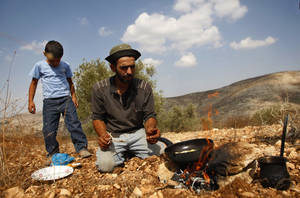 Photo -   In this photograph made on Monday, Oct. 22, 2012, a Palestinian farmer Khader Khader, 31, cooks food on his land in Nisf Jubeil, near the West Bank city of Nablus. In an emerging back-to-the-land movement, Palestinian farmers are turning the rocky hills of the West Bank into organic olive groves, selling their oil to high-end grocers in the U.S. and Europe. (AP Photo/Majdi Mohammed).