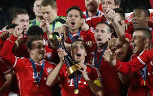Photo - Bayern's team captain Philipp Lahm, center, lift the trophy after winning the final of the soccer Club World Cup between FC Bayern Munich and Raja Casablanca in Marrakech, Morocco, Saturday, Dec. 21, 2013. (AP Photo/Matthias Schrader)