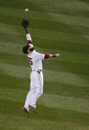 Photo - Boston Red Sox second baseman Dustin Pedroia leaps, but can't field a hit by Detroit Tigers' Omar Infante in the second inning during Game 6 of the American League baseball championship series on Saturday, Oct. 19, 2013, in Boston.  (AP Photo/Elise Amendola)