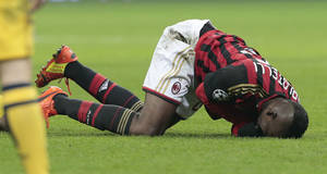 Photo - AC Milan's forward Mario Balotelli, lays on the turf after he injured himself in a collision during a round of 16th Champions League soccer match between AC Milan and Atletico Madrid at the San Siro stadium in Milan, Italy, Wednesday, Feb. 19, 2014. (AP Photo/Emilio Andreoli)