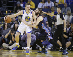 Photo - Golden State Warriors' David Lee (10) looks to drive against Charlotte Bobcats' Josh McRoberts (11) during the first half of an NBA basketball game in Oakland, Calif., Tuesday, Feb. 4, 2014. (AP Photo/Tony Avelar)