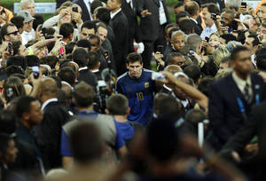 Photo - Argentina's Lionel Messi walks up the tribune to collect the second place trophy after the World Cup final soccer match between Germany and Argentina at the Maracana Stadium in Rio de Janeiro, Brazil, Sunday, July 13, 2014. Germany won 1-0. Germany won 1-0.(AP Photo/Hassan Ammar)