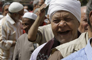 Photo -   An Egyptian man smiles as he waits in line to vote in the presidential election Wednesday, May 23, 2012, outside a polling station in Cairo, Egypt. Nearly a year and a half after the ouster of autocratic leader Hosni Mubarak, millions of Egyptians lined up for hours outside polling stations Wednesday to freely choose a president for the first time in an election that pits old regime figures promising stability against ascending Islamists seeking to consolidate power. (AP Photo/Hasan Jamali)