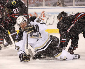 Photo - Pittsburgh Penguins center Sidney Crosby (87) falls to the ice after being checked by Chicago Blackhawks center Jonathan Toews, right, during the first period of an NHL Stadium Series hockey game at Soldier Field on Saturday, March 1, 2014, in Chicago. (AP Photo/Charles Rex Arbogast)