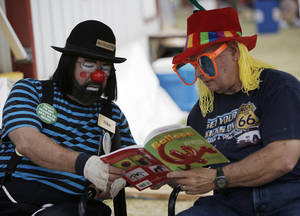 "photo - Clowns Nick ""Niko"" Garrity and John ""Banjo"" Trivette look over a balloon book at the Oklahoma State Fair, Sunday, Sept. 23, 2012.  Photo by Garett Fisbeck, The Oklahoman"