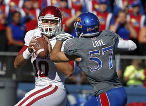 Photo - Oklahoma quarterback Blake Bell (10) looks for a receiver while pressured by Kansas linebacker Jake Love (57) during the first half of an NCAA college football game in Lawrence, Kan., Saturday, Oct. 19, 2013. (AP Photo/Orlin Wagner)